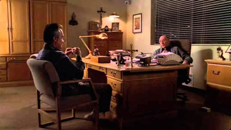 Paulie Walnuts talks with the priest in The Sopranos
