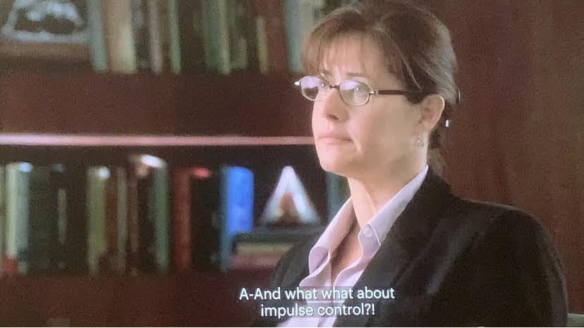 Dr. Melfi is sitting in her office with her hair up and glasses on talking to Tony.