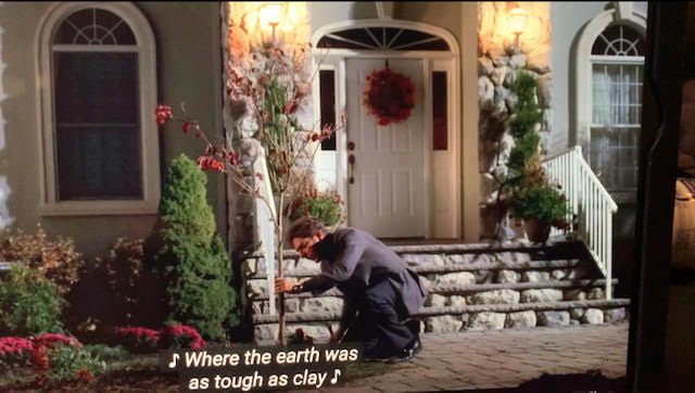christopher moltisanti is fixing a plant right in front of his big house.