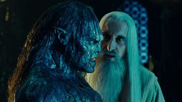 Saruman the White stands next to an orc covered in goo.