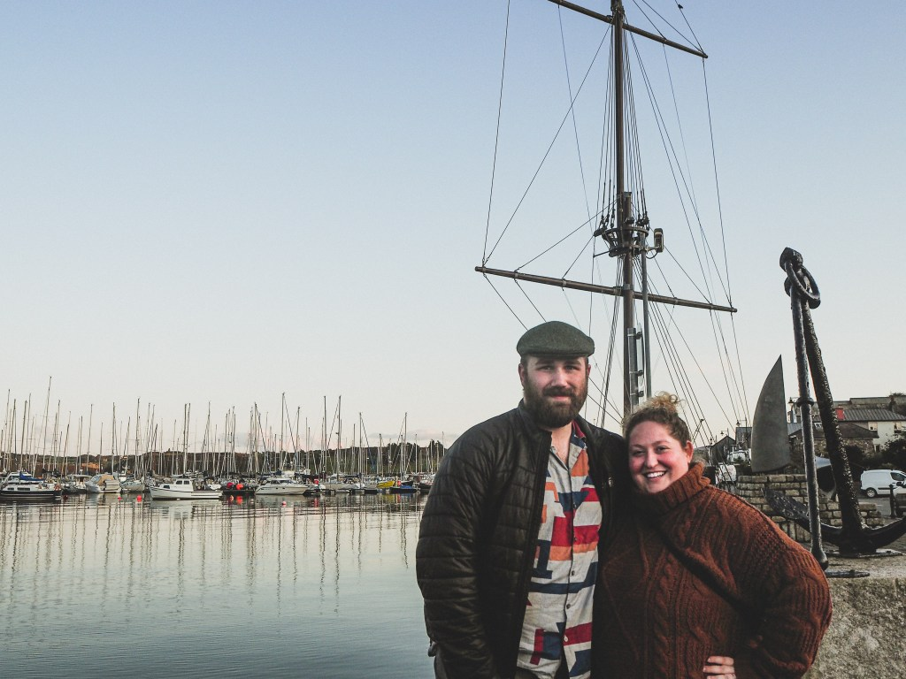 Sorcha and Matt in front of the Marina in Kinsale harbor at sunset. Sorcha is wearing a rusty brown chunky knit turtleneck sweater. Matt is wearing a black puffy jacket green hat, and red and orange patterned top.
