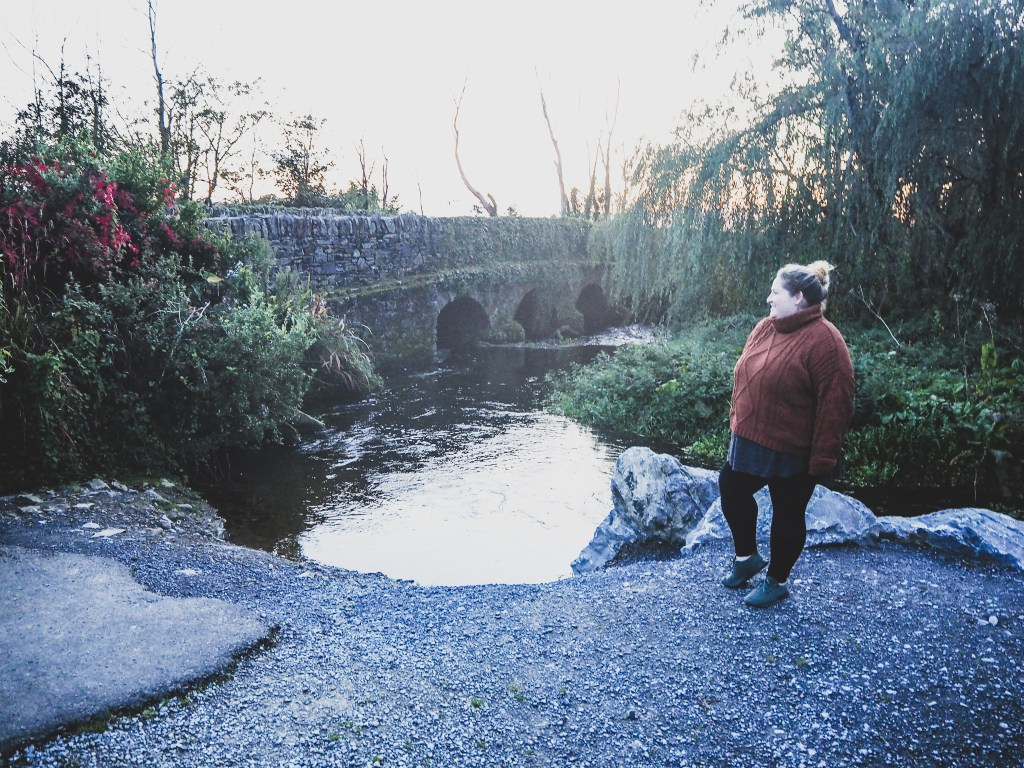 Sorcha is looking out over a river she and Matt came across while driving through county Cork. There is a crumbling rustic stone bridge going over the river and the sun is setting creating a warm glow. Sorcha is wearing black leggings, a long grey tunic, and a chunky knit rust colored turtleneck sweater.