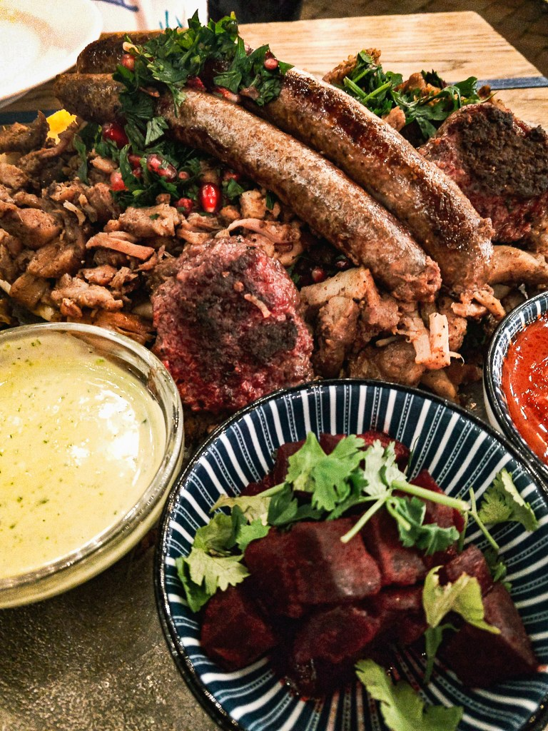 heaping pile of assorted spiced Mediterranean meats with colorful sauces of red pepper, and garlic cream, and a pile of diced pickled purple beets with cilantro garnish.