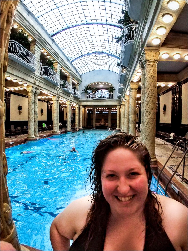 Sorcha smiling with the Gellert Spas sky blue pool behind. Lined with columns decorated with stone etched vines and green plants draping over the balcony above.