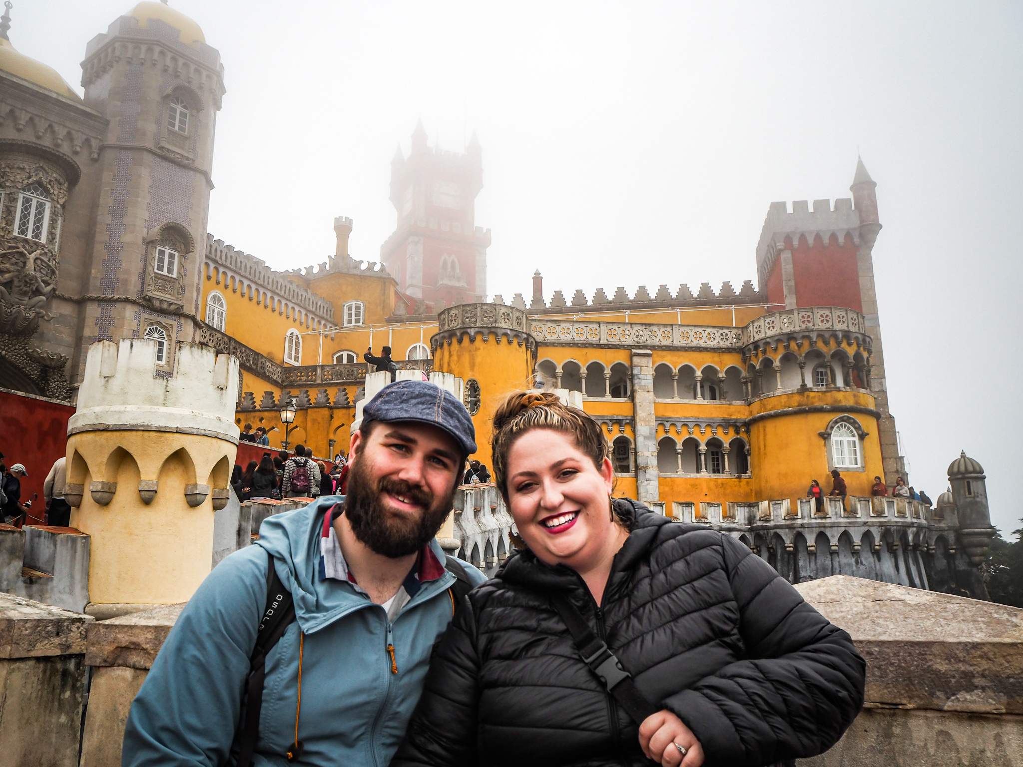 Sorcha and Matt in front of the red, purple and yellow towers of the Moorish Pena Palace