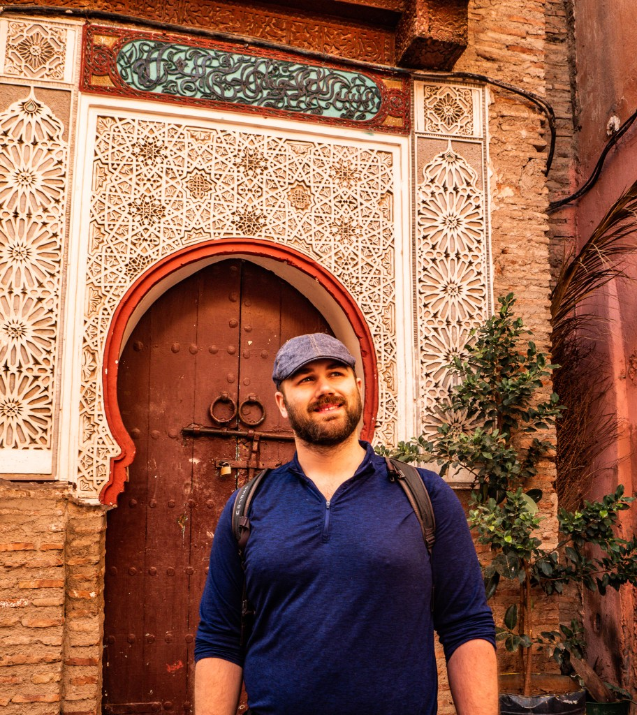 Matthew in front of an ornate wood carved doorway with rounded arched entrance and trees around. Matt is smiling, wearing a blue shirt and hat and looking off into the distance.