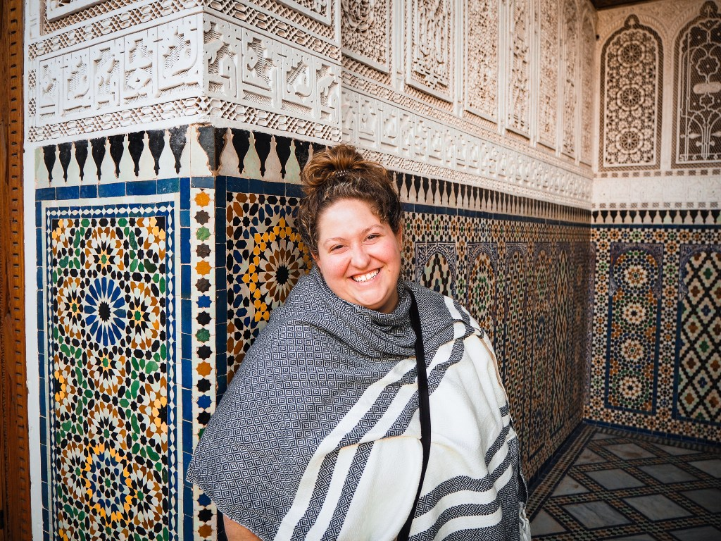 sorcha standing in front of a multicolored tile wall with ornate marble carvings her hair is in a bun, the photo is shot from the waist up and she's smiling at the camera wearing a black and white striped shawl.