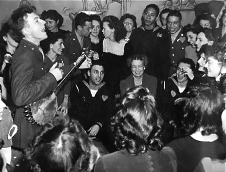 Seeger entertaining a group that includes First Lady Eleanor Roosevelt.