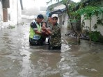 Babinsa dari jajaran Koramil Kodim Jombang bersama relawan membantu evakuasi warga yang terdampak banjir