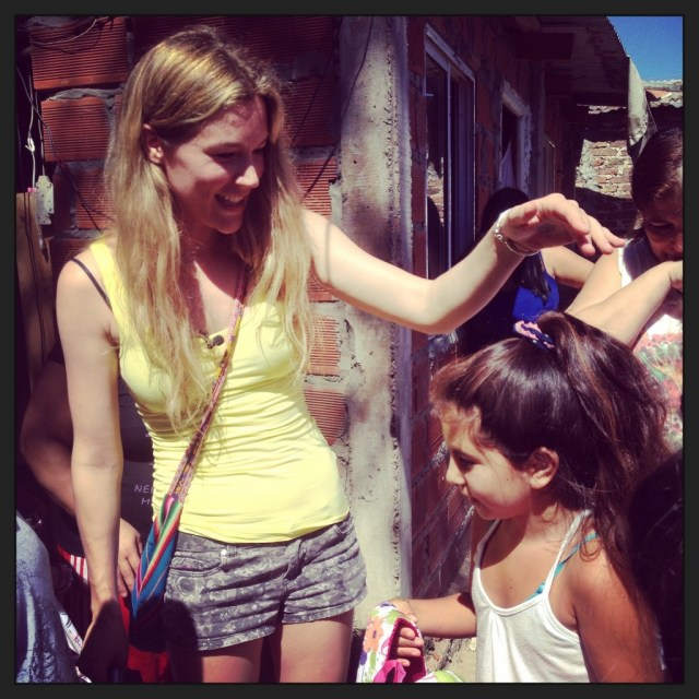 Joss Stone gives out a rucksack to a young girl in Villa La Cárcova. Ph: Sorrel Moseley-Williams