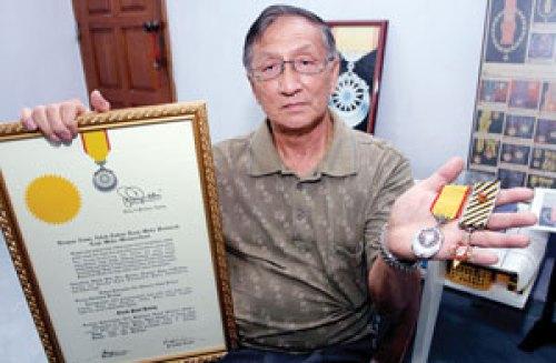 Paul Kiong menunjukkan pingat yang dimilikinya. Imej dari Utusan.
