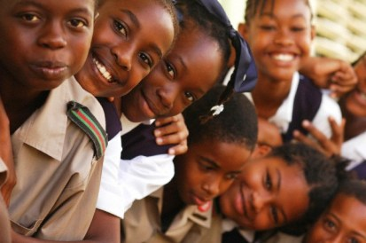 13 Jan 2011, Barbados --- Close-up of African schoolchildren smiling, standing one behind another, wearing school uniform --- Image by © Stephanie Rabemiafara/Art in All of Us/Corbis