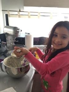 Ayudando a su nina a hacer pancakes.