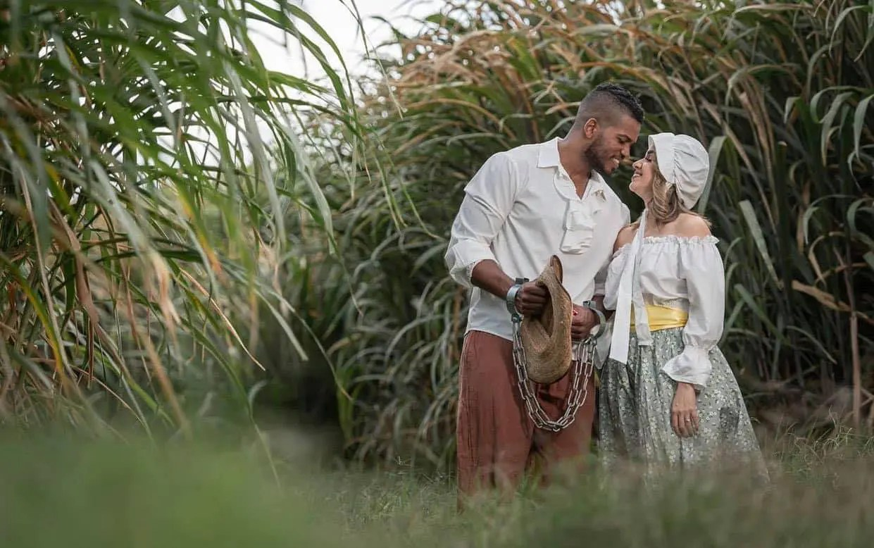 A Black slave man romantically close face-to-face with a White woman in a field.