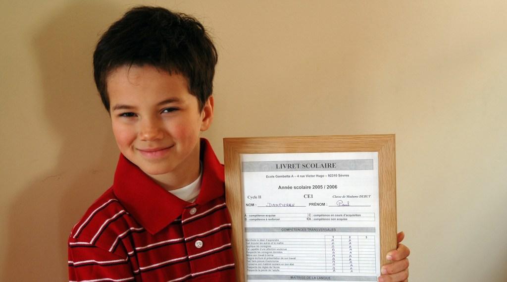Boy showing his school grades