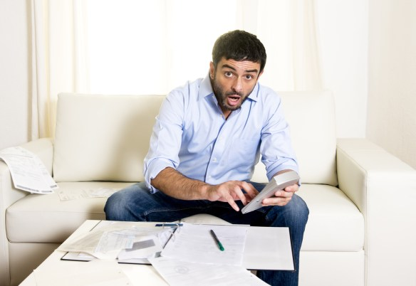 latin business man worried paying bills on couch