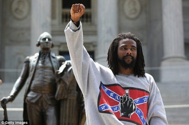 Countering: A man holds a black power salute during the Black Educators for Justice rally, which has ties with The New Black Panther Party, on Saturday. His sweater sends a message to the pro-Confederate marchers