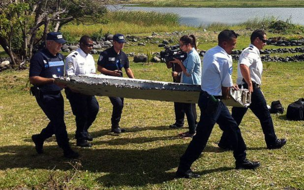 Police carry a piece of debris from an unidentified aircraft found in the coastal area of Saint-Andre de la Reunion (AFP/Getty Images)