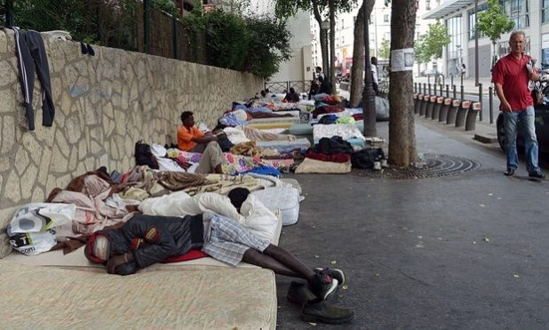 Migrants sleep on mattresses on the pavement in a makeshift camp in Paris. Photograph: Guillemette Villemin/Getty Images