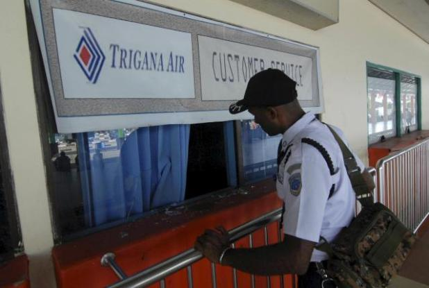 A security guard checks on the Trigana Air service counter that was damaged by angry family members of passengers from the missing Trigana Air flight at the airport in Sentani, near Jayapura, Papua province, Indonesia August 17, 2015 in this photo taken by Antara Foto.REUTERS/ Lucky R. /Antara Foto
