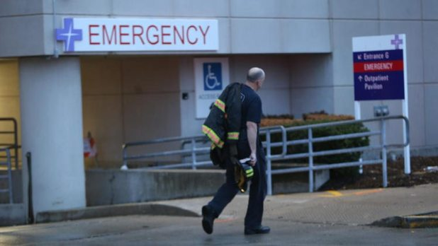 A firefighter walks past the emergency room at Christ Hospital as emergency personnel gather for the procession that will take the body of a firefigher who died from injuries sustained in an overnight fire to the Cook County Medical Examiner on Monday, December 14, 2015. (Antonio Perez / Chicago Tribune)