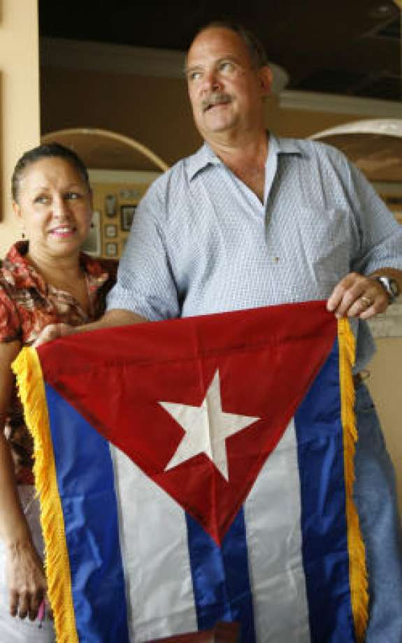 A file photo of the late Guido Piquet, right, owner of Cafe Piquet on Bissonnet, and his wife, Nelly, holding a Cuban flag that was given to them several years ago.
