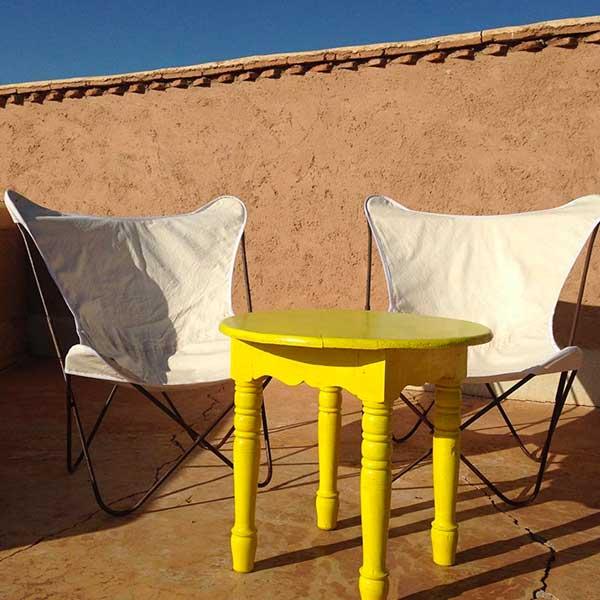 Sitzecke mit gelbem Tisch und weißen Schmetterlingsstühlen