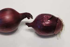 Peel and cut two red onions in half.