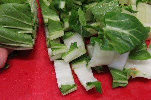 Slice the stalk end of the pok choy quiet thin.