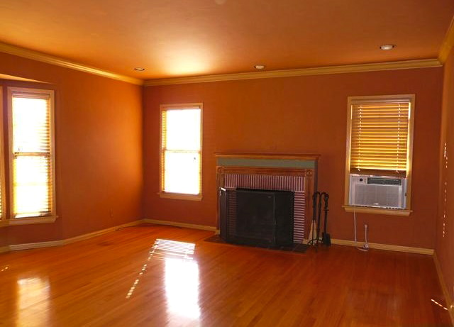 Living room with original wood floors, double hung windows and fireplace