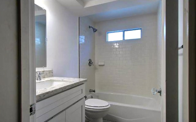 Remodeled bath with marble vanity and subway tile shower