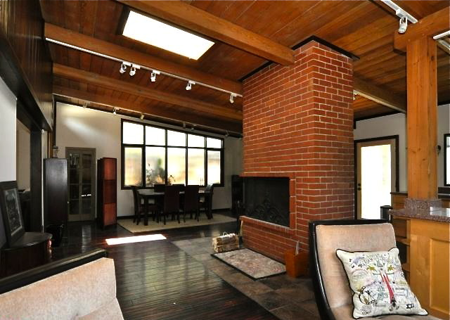 Living room with beamed/vaulted ceilings, skylight and floor-to-ceiling fireplace
