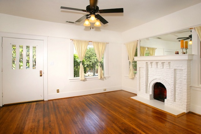 Living room with original wood floors and stone fireplace