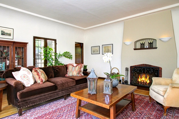 Living room with picture window, fireplace and original wood floors