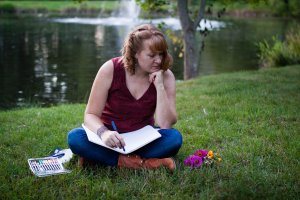 woman sitting near lake thinking with a notebook in her lap looking at flowers