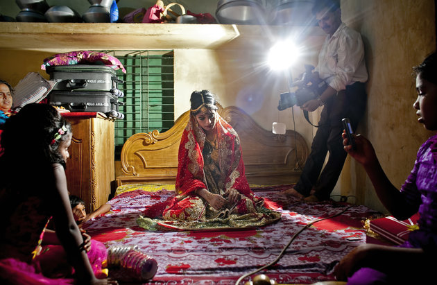 """MANIKGANJ, BANGLADESH - AUGUST 20: 15 year old Nasoin Akhter poses for a video on the day of her wedding to a 32 year old man, August 20, 2015 in Manikganj, Bangladesh.  In June of this year, Human Rights Watch released a damning report about child marriage in Bangladesh. The country has one of the highest rates of child marriage in the world, with 29% of girls marrying before the age of 15, and 65% of girls marrying before they turn 18. The detrimental effects of early marriage on a girl cannot be overstated. Most young brides drop out of school. Pregnant girls from 15-20 are twice as likely to die in childbirth than those 20 or older, while girls under 15 are at five times the risk. Research cites spousal age difference as a significant risk factor for violence and sexual abuse. Child marriage is attributed to both cultural tradition and poverty. Parents believe that it """"protects"""" girls from sexual assault and harassment. Larger  dowries are not required for young girls, and economically, women's earnings are insignificant as compared to men's. (Photo by Allison Joyce/Getty Images)"""