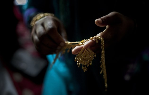 """MANIKGANJ, BANGLADESH - AUGUST 20:  Gold wedding jewelry is laid out for 15 year old Nasoin Akhter on the day of her wedding to a 32 year old man, August 20, 2015 in Manikganj, Bangladesh.  In June of this year, Human Rights Watch released a damning report about child marriage in Bangladesh. The country has one of the highest rates of child marriage in the world, with 29% of girls marrying before the age of 15, and 65% of girls marrying before they turn 18. The detrimental effects of early marriage on a girl cannot be overstated. Most young brides drop out of school. Pregnant girls from 15-20 are twice as likely to die in childbirth than those 20 or older, while girls under 15 are at five times the risk. Research cites spousal age difference as a significant risk factor for violence and sexual abuse. Child marriage is attributed to both cultural tradition and poverty. Parents believe that it """"protects"""" girls from sexual assault and harassment. Larger  dowries are not required for young girls, and economically, women's earnings are insignificant as compared to men's. (Photo by Allison Joyce/Getty Images)"""
