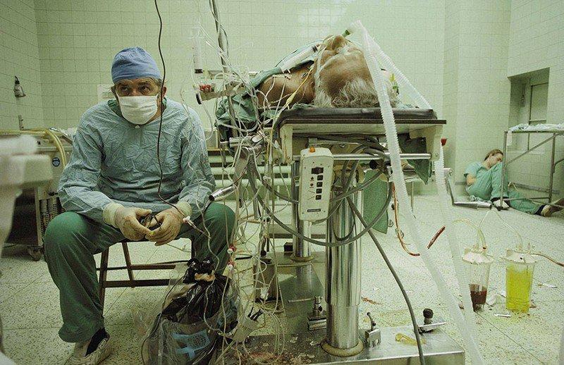Кардиохирург после успешной 23-часовой трансплантации сердца. Его помощник спит в углу