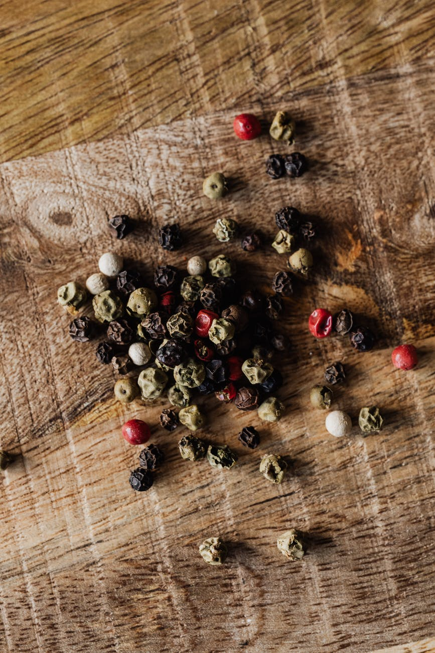 mix of pepper seeds on wooden surface