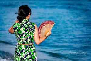 Woman on sandy beach, blue ocean water, strolling with a fan