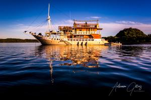Stunning topside imagery, Boat Mikumba Dua on blue water with reflection in golden light