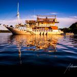 Boat Mikumba Dua on blue water with reflection in golden light