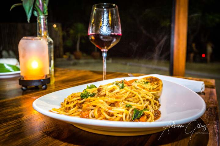 Spaghetti bolognese and a glass of red wine on a candle lit table for two at night