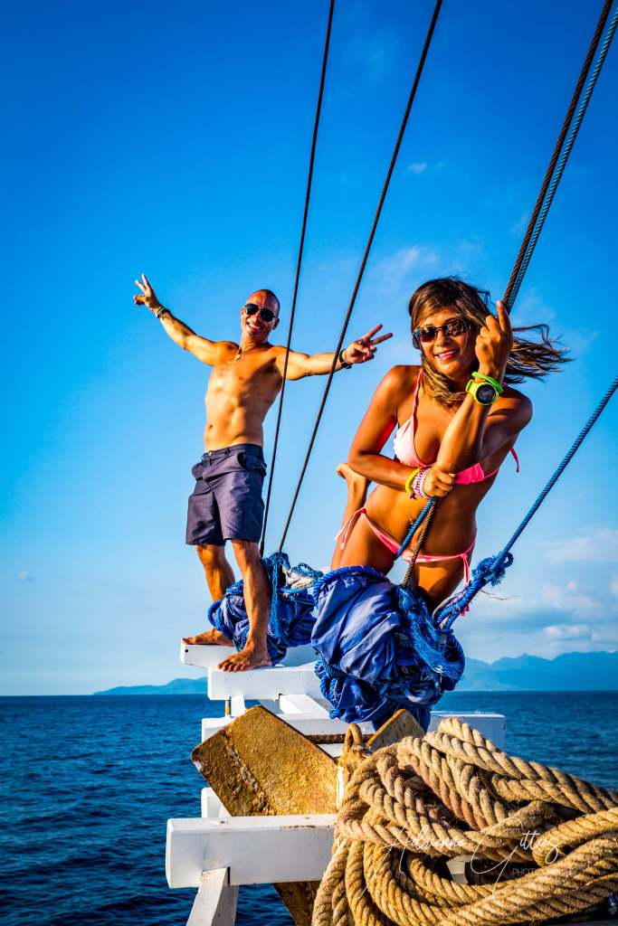Beautiful girl in pink bikini and handsome man on bow of boat