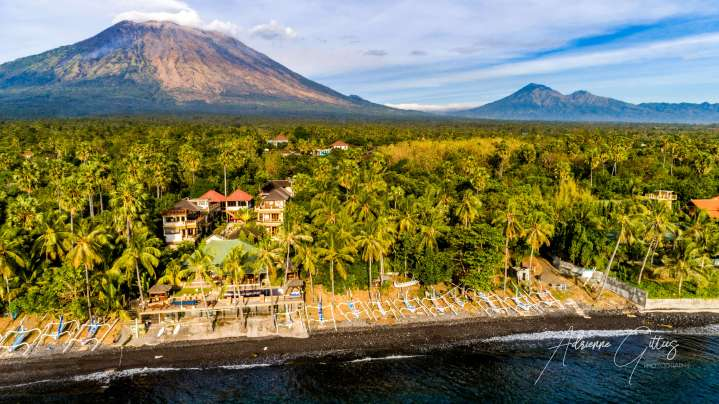 Drone shot of Mount Agung volcano, palm trees, lush green landscape, Bali, Indonesia