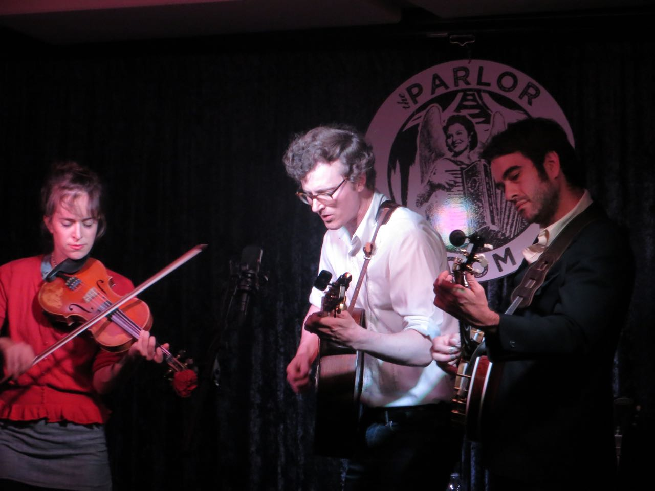 Michael Daves singing/guitar, Brittany Haas -violin, Noam Pikelny -banjo on stage; Parlor Room logo in background