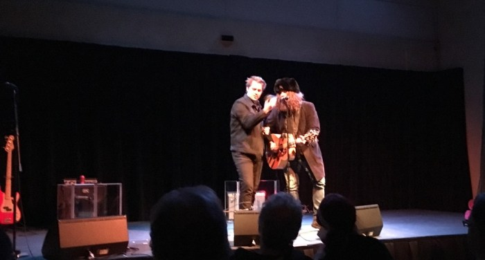 Lee Harvey Osmond, Tom Wilson on guitar, Thompson Wilson around a microphone on stage at the WAMC Auditorium, Albany
