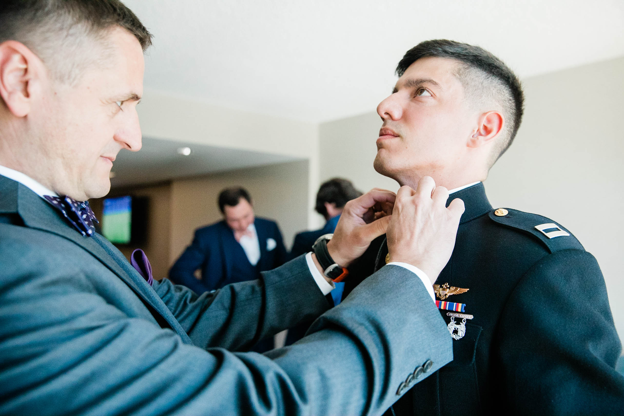 seattle wedding photographer captures groom putting on bowtie before marriage ceremony