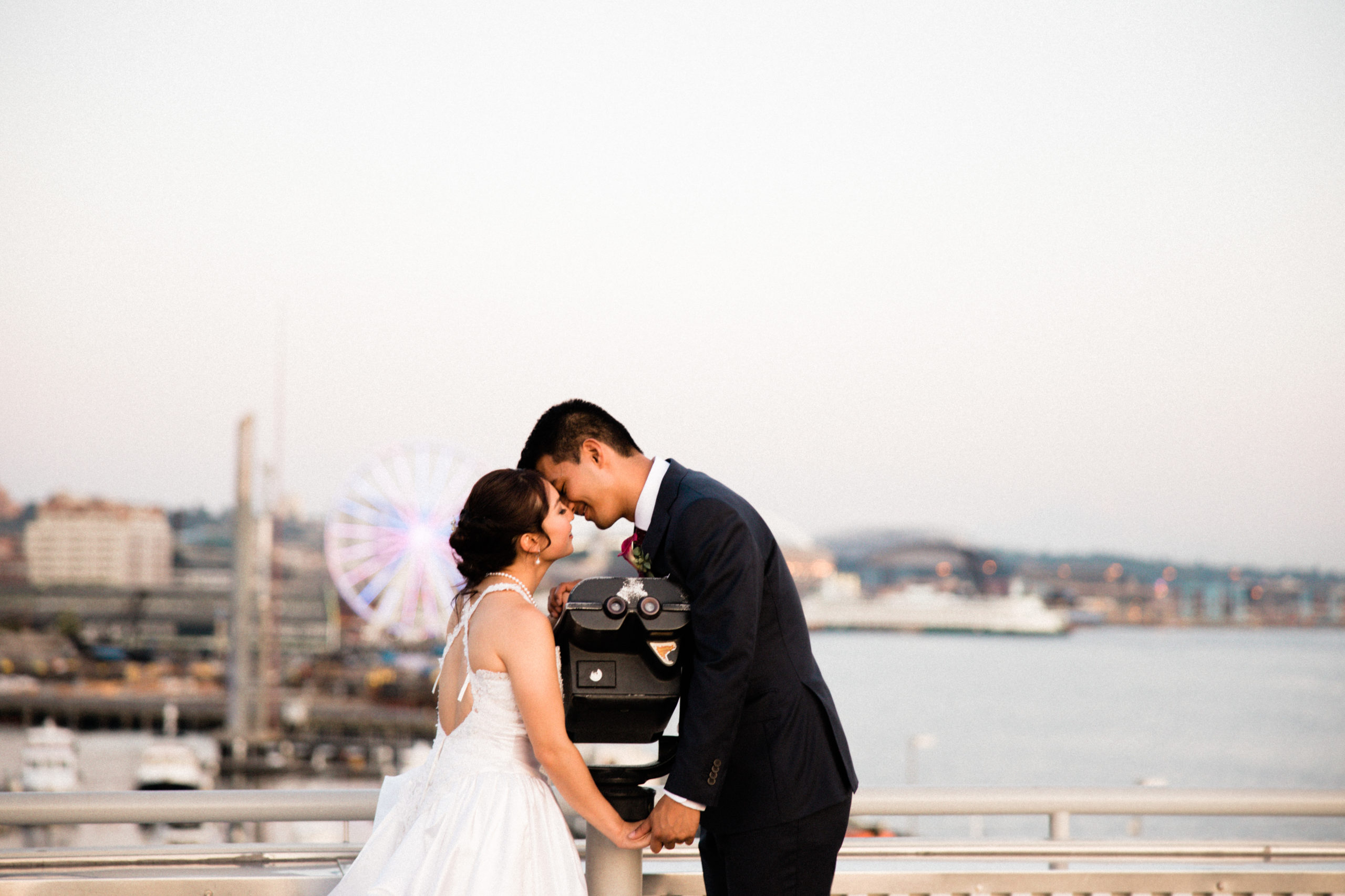 couples photos outside edgewater hotel with seattle great wheel and ferries in the distance