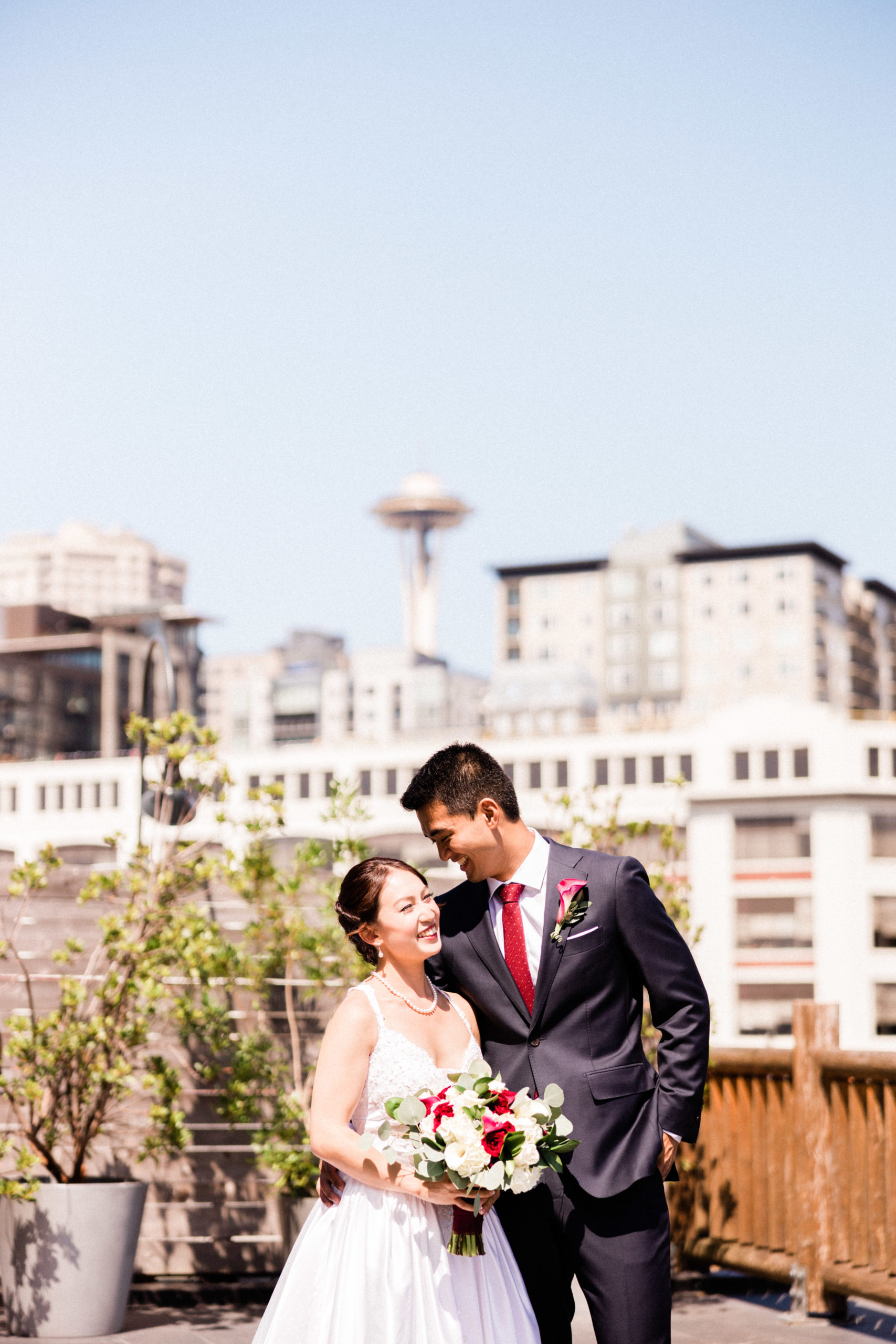 bride and groom with seattle space needle in distance on balcony of edgewater hotel